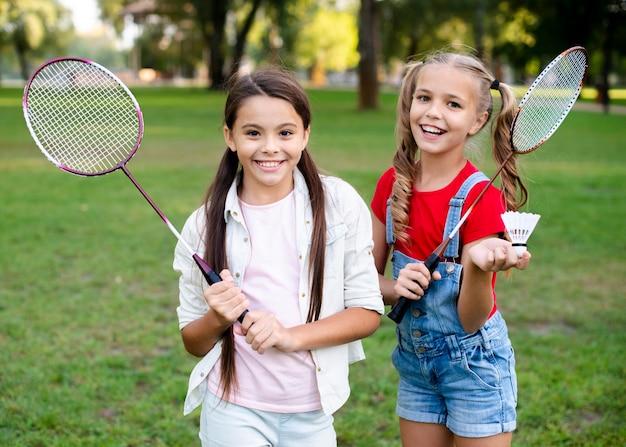 Cheerful girls holding badminton rackets in hand Free Photo