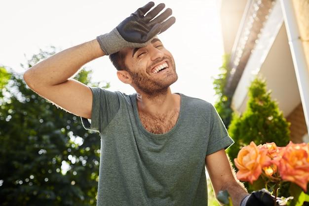 Веселый красивый молодой кавказский человек в синей футболке и перчатках, улыбаясь с зубами, устал от тяжелой работы в саду. фермер сажает листья в загородном доме Бесплатные Фотографии