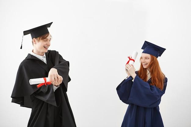 Веселые выпускники улыбаются, борются с дипломами. Бесплатные Фотографии