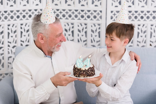 Cheerful grandfather and grandson looking at each other while holding delicious cake with candle Free Photo
