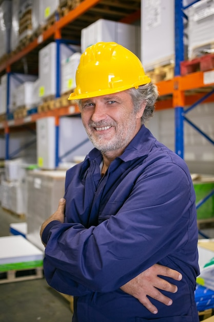 Allegro lavoratore logistico dai capelli grigi in elmetto protettivo e uniforme in piedi a scaffali in magazzino con le braccia conserte, che guarda l'obbiettivo e sorridente. colpo verticale. concetto di ritratto di colletti blu e lavoro Foto Gratuite