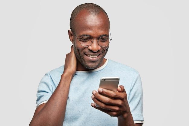 Веселый парень болтает на смартфоне с другом или девушкой, получает хорошие новости в сообщениях, держит современный мобильный телефон Бесплатные Фотографии