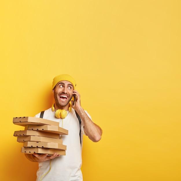 Ragazzo allegro consegna scatole di pizza dal ristorante, chiama il cliente tramite smartphone, guarda volentieri da parte, vestito con abiti casual, posa contro il muro giallo. consegne alimentari e lavoro di corriere Foto Gratuite