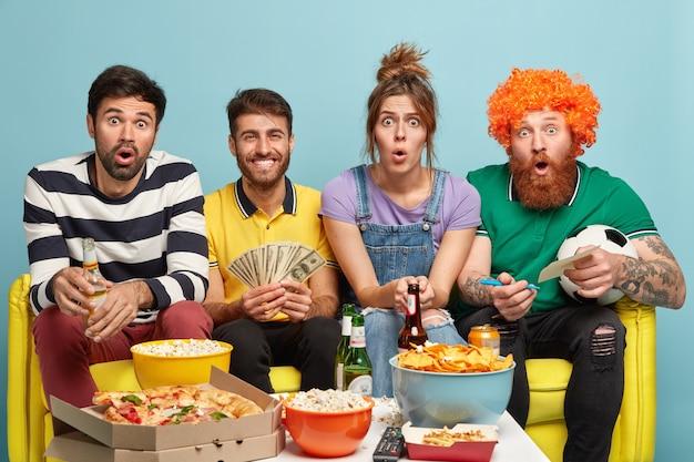 陽気な男はお金の紙幣に束を持ち、サッカーの試合結果に賭け、おいしいピザを食べ、冷たいビールを飲み、ソファで一緒にポーズをとります。スポーツトーナメントを見ながら4人の友人がギャンブル 無料写真