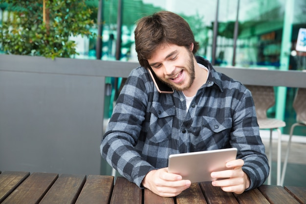 Cheerful guy watching video on gadget screen Free Photo