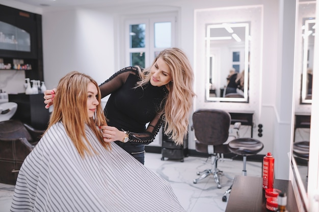 Cheerful hairdresser talking to client | Free Photo