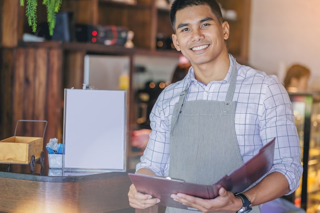 Cheerful handsome business owner standing with invite present menu in front of bar. Premium Photo