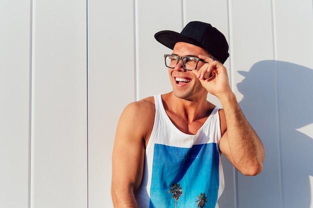 Cheerful handsome guy in eyeglasses posing near the urban wall, wearing t-shirt sleeveless Free Photo