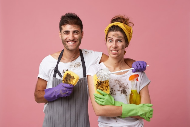 Cheerful handsome male wearing protective gloves and apron holding dirty sponge embracing his wife Free Photo