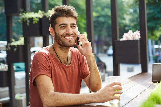 Cheerful handsome man laughing and smiling while talking on mobile phone from outdoor cafe Free Photo