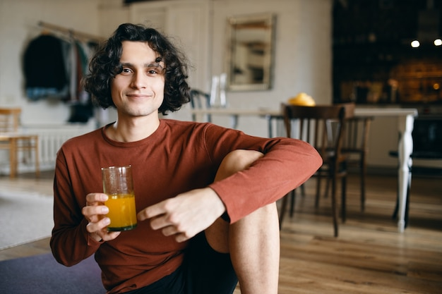 Allegro bel giovane uomo seduto sul pavimento, avendo arancia fresca per colazione essendo su succo di frutta a digiuno, sorridendo felicemente alla telecamera Foto Gratuite