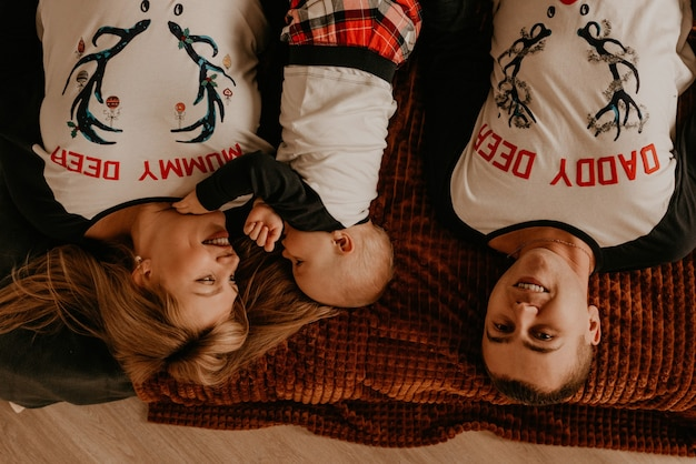 Веселая счастливая семья в пижаме с ребенком лежат на кровати в спальне. новогодняя семейная одежда смотрится нарядами. подарки на день святого валентина Premium Фотографии