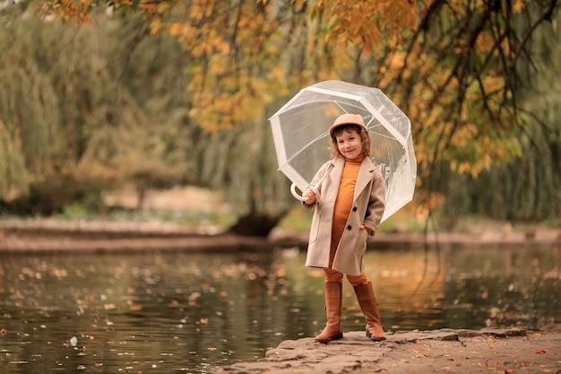 Веселая счастливая девушка с прозрачным зонтиком на прогулке осенью у озера Premium Фотографии