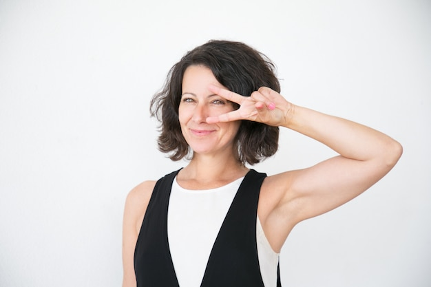 Cheerful happy woman in casual showing peace sign Free Photo