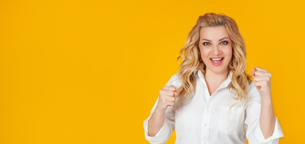 Cheerful, happy woman raising her hands with her fist, cheering for the team, winning a huge bet, playing in the casino in delight Premium Photo