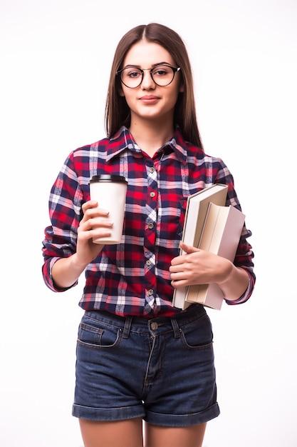 Allegra donna felice con un sorriso a trentadue denti, porta caffè da asporto e libro rosso, felice di finire lo studio Foto Gratuite