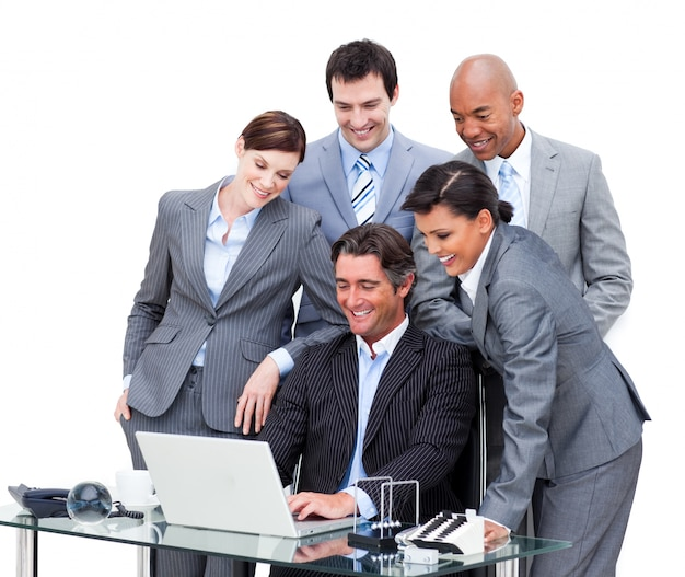 Cheerful international business team looking at a laptop Premium Photo
