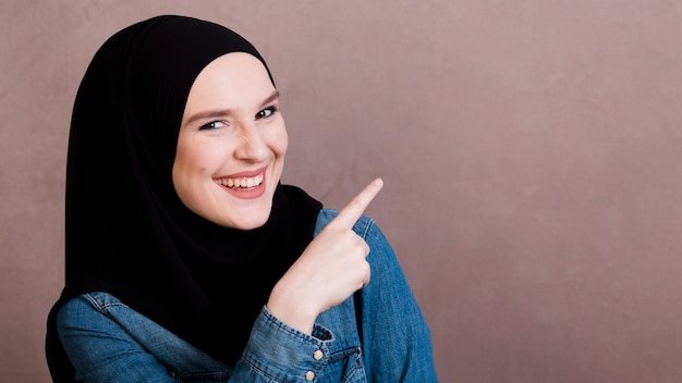 Cheerful islamic woman pointing her finger at something Free Photo