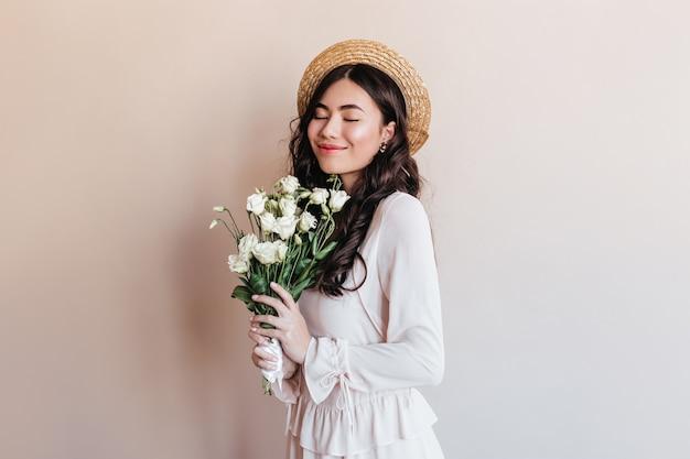 花を持っている陽気な日本人女性。花束と麦わら帽子でスタイリッシュなアジアのモデルのスタジオショット。 無料写真