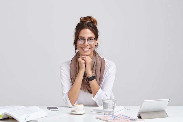 Giornalista allegro con un aspetto gradevole, indossa occhiali trasparenti, ha i capelli scuri pettinati, arricchisce le sue conoscenze durante la lettura, ha un tenero sorriso seduto nell'area di lavoro con touchpad, bicchiere d'acqua Foto Gratuite