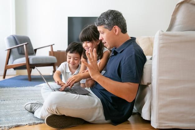 Веселые дети и взволнованный папа вместе используют ноутбук, сидя на полу в квартире, просматривая интернет. Бесплатные Фотографии