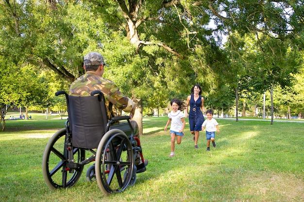陽気な子供たちとその母親が軍の父に会い、カモフラージュで障害者の男に走っています。戦争のベテランまたは帰国の概念 無料写真