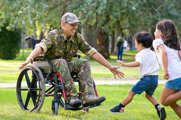 陽気な子供たちは軍のお父さんに会い、抱擁のために両手を広げてカモフラージュで障害者の男に走っています。戦争のベテランまたは帰国の概念 無料写真