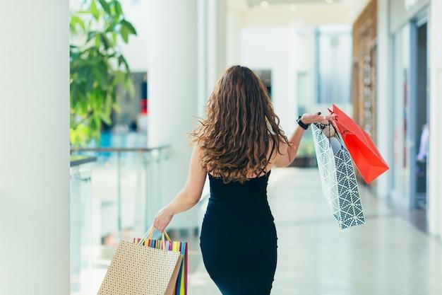 店内を歩きながら色とりどりの買い物袋を背負ってスタイリッシュな黒のドレスを着た陽気な女性。 Premium写真