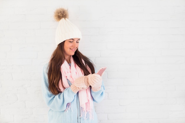 Cheerful lady in mittens, bobble hat and scarf with smartphone Free Photo