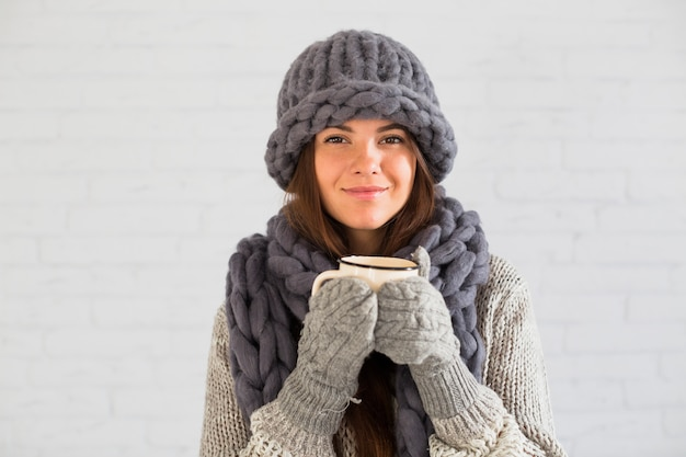 Cheerful lady in mittens, hat and scarf with cup in hands Free Photo