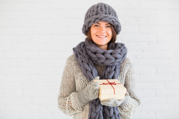 Cheerful lady in mittens, hat and scarf with present box Free Photo