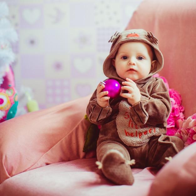 クリスマスツリーの近くで遊んでいる明るい小さな赤ちゃん 無料写真