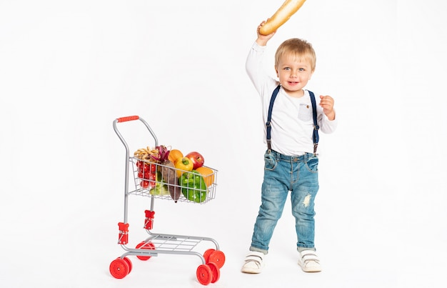 Cheerful little boy in casual clothes standing in studio with healthy food basket. shopping, discount, sale concept Premium Photo
