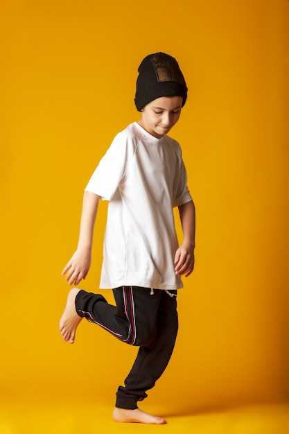 Веселый мальчик, одетый в спортивные штаны и белую футболку, активно танцует, стоит на желтом фоне Premium Фотографии
