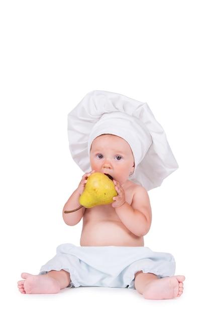 白のシェフのスーツを着た彼の手に梨を持つ陽気な小さな子供。 Premium写真