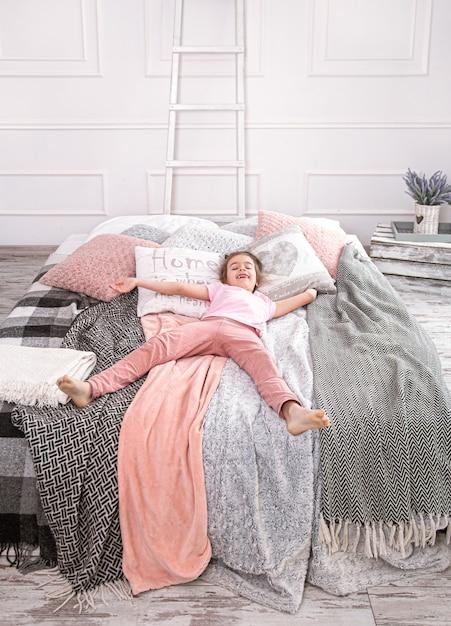 Веселая маленькая девочка лежит на кровати с красивыми одеялами и подушками. Premium Фотографии