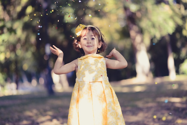 Cheerful little girl playing with confetti Free Photo