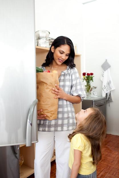 Веселая девочка распаковывает продуктовый портфель с матерью Premium Фотографии