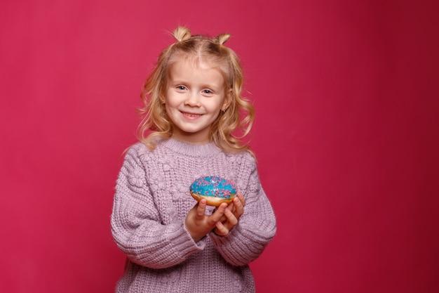 도넛과 명랑 소녀입니다. 아이는 음식에 빠지다. 도넛과 재미 프리미엄 사진