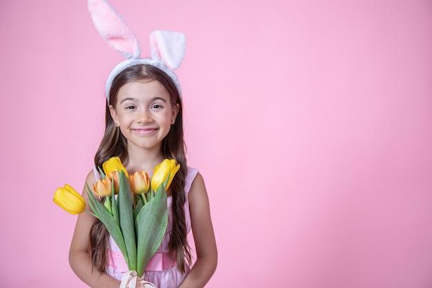 Веселая маленькая девочка с ушками пасхального кролика улыбается и держит в руках букет тюльпанов в розовой студии Бесплатные Фотографии