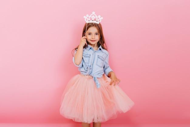 ピンクの背景に分離された頭の上の王女の王冠を保持しているチュールスカートで長いブルネットの髪を持つ陽気な少女。子供のための明るいカーニバル、誕生日パーティーを祝って、かわいい子供を楽しんで 無料写真