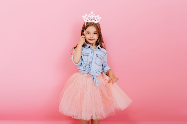 Cheerful little girl with long brunette hair in tulle skirt holding princess crown on head  isolated on pink background. celebrating brightful carnival for kids, birthday party, having fun of cute kid Free Photo