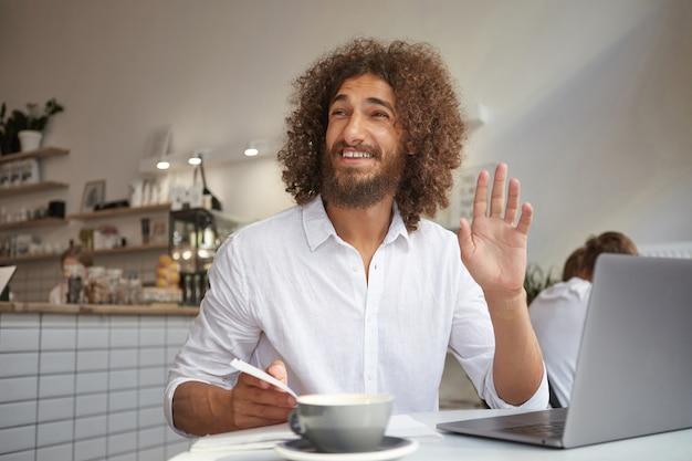 Веселый симпатичный кудрявый мужчина с бородой встречает знакомого человека и машет рукой, работает удаленно с ноутбуком, позирует над интерьером завтрака Бесплатные Фотографии