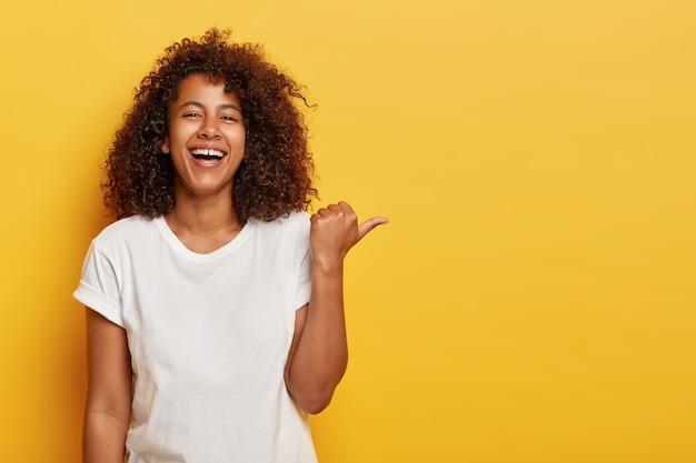 La ragazza allegra e adorabile punta il pollice di lato, ride allegramente, ha un sorriso luminoso, dimostra qualcosa di bello, si sente divertita, è di ottimo spirito, indossa una maglietta bianca, posa contro un muro giallo Foto Gratuite