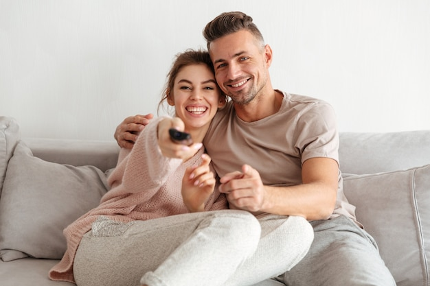 Cheerful loving couple sitting on couch together and watching tv Free Photo