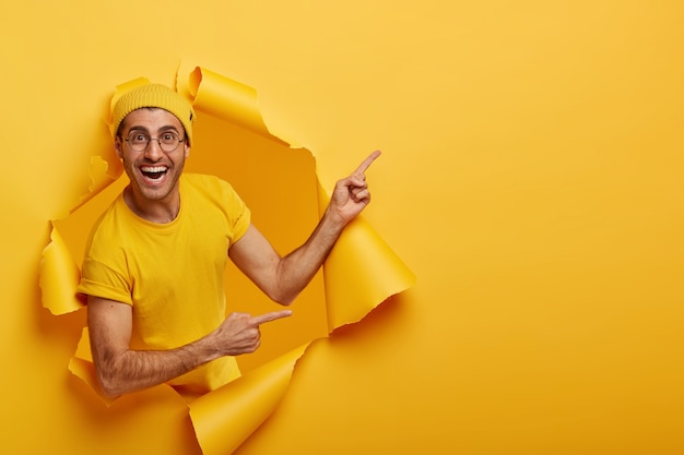 Cheerful male gives nice offer, advertises new product on sale, stands in torn paper hole, has positive expression Free Photo