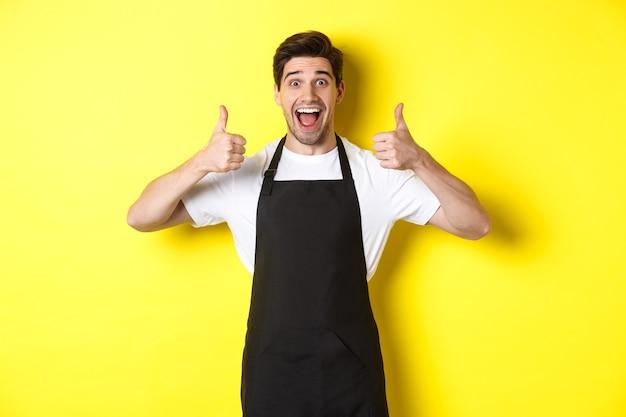 Веселый человек-бариста в черном фартуке показывает палец вверх, рекомендует кафе или ресторан, стоя Premium Фотографии