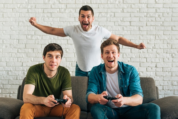 Cheerful man cheering for the friends playing video game at home Free Photo