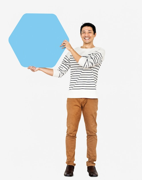 Cheerful man showing a blank blue hexagon board Free Photo