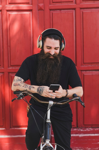 Cheerful man sitting on bicycle using mobile phone and headphones Free Photo